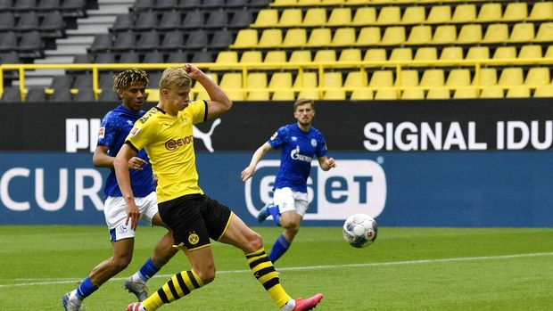 Dortmund's Erling Haaland scores the opening goal during the German Bundesliga soccer match between Borussia Dortmund and Schalke 04 in Dortmund, Germany, Saturday, May 16, 2020. The German Bundesliga becomes the world's first major soccer league to resume after a two-month suspension because of the coronavirus pandemic. (AP Photo/Martin Meissner, Pool)