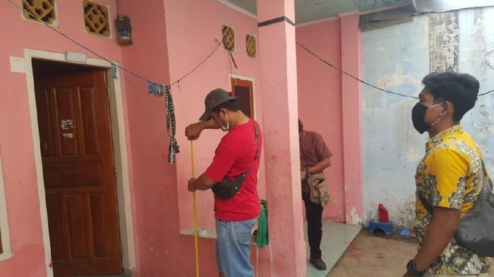 Polisi mengukur ketinggian jemuran yang digunakan untuk menggantung korban
