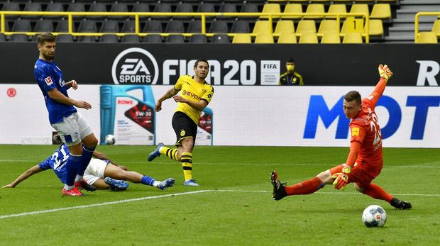 Dortmund's Raphael Guerreiro, center, scores his side's second goal during the German Bundesliga soccer match between Borussia Dortmund and Schalke 04 in Dortmund, Germany, Saturday, May 16, 2020. The German Bundesliga becomes the world's first major soccer league to resume after a two-month suspension because of the coronavirus pandemic. (AP Photo/Martin Meissner, Pool)