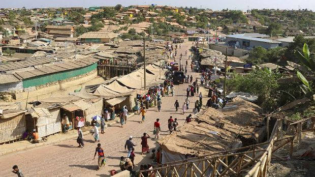 Rohingya refugees walk through one of the arterial roads at the Kutupalong refugee camp in Cox's Bazar, Bangladesh. Authorities on Thursday, May 14, 2020 reported the first coronavirus case in the crowded camps for Rohingya refugees in southern Bangladesh, where more than 1 million refugees have been sheltered, a Bangladeshi official and the United Nations said. (AP Photo/Shafiqur Rahman, File)