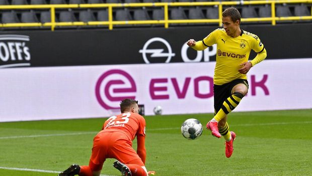 Dortmund's Thorgan Hazard scores his side's third goal during the German Bundesliga soccer match between Borussia Dortmund and Schalke 04 in Dortmund, Germany, Saturday, May 16, 2020. The German Bundesliga becomes the world's first major soccer league to resume after a two-month suspension because of the coronavirus pandemic. (AP Photo/Martin Meissner, Pool)
