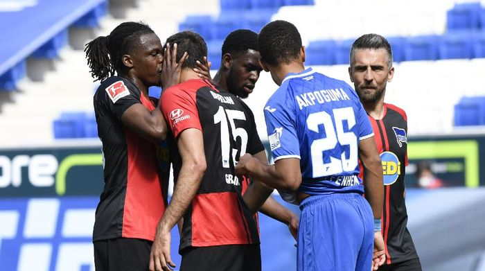 SINSHEIM, GERMANY - MAY 16: Dedryck Boyata of TSG 1899 Hoffenheim talks to teammate Serbian Marko Grujic during the Bundesliga match between TSG 1899 Hoffenheim and Hertha BSC at PreZero-Arena on May 16, 2020 in Sinsheim, Germany. The Bundesliga and Second Bundesliga is the first professional league to resume the season after the nationwide lockdown due to the ongoing Coronavirus (COVID-19) pandemic. All matches until the end of the season will be played behind closed doors. (Photo by Thomas Kienzle/Pool via Getty Images)