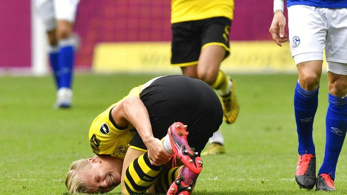 Dortmunds Erling Haaland grimaces after being fouled during the German Bundesliga soccer match between Borussia Dortmund and Schalke 04 in Dortmund, Germany, Saturday, May 16, 2020. The German Bundesliga becomes the worlds first major soccer league to resume after a two-month suspension because of the coronavirus pandemic. (AP Photo/Martin Meissner, Pool)