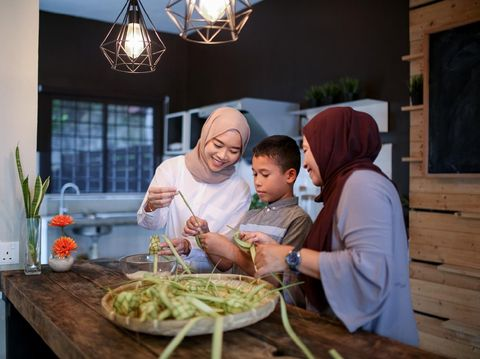 Mother and sister with brother making food in kitchen during eid celebration in Malaysia