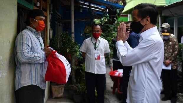 Presiden Joko Widodo (kanan) memberi salam kepada warga saat meninjau proses distribusi sembako tahap ketiga bagi masyarakat kurang mampu dan terdampak COVID-19 di kawasan Johar Baru, Jakarta Pusat, Senin (18/5/2020). ANTARA FOTO/Sigid Kurniawan/wsj.