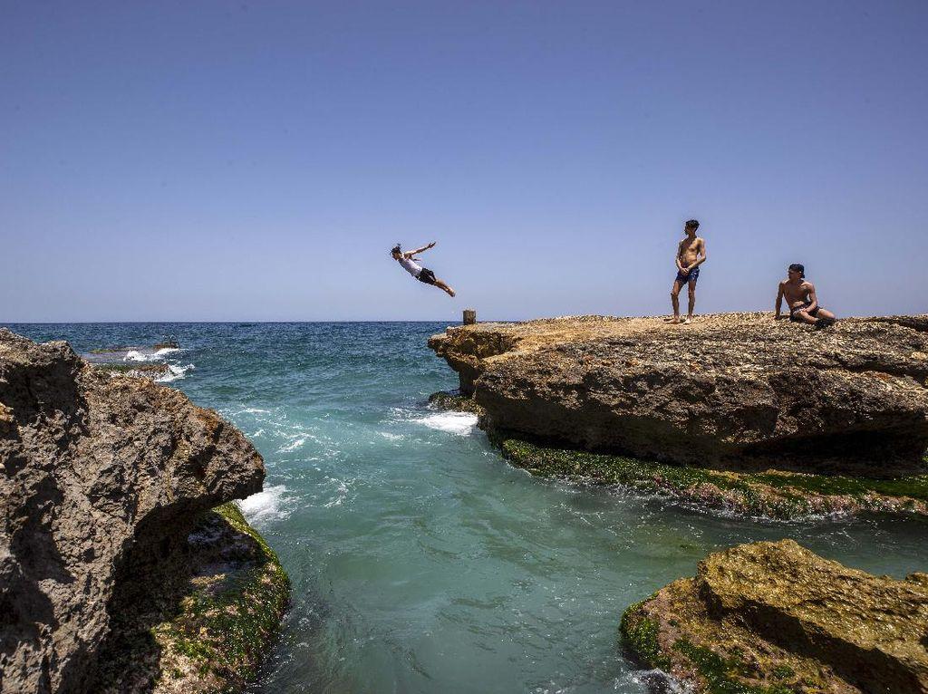 Asyiknya Warga Libanon Melompat dan Memacing di Laut Mediterania