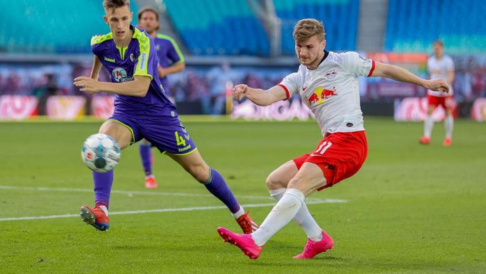 LEIPZIG, GERMANY - MAY 16: Timo Werner of RB Leipzig shoots past Nico Schlotterbeck of Sport-Club Freiburg during the Bundesliga match between RB Leipzig and Sport-Club Freiburg at Red Bull Arena on May 16, 2020 in Leipzig, Germany. The Bundesliga and Second Bundesliga is the first professional league to resume the season after the nationwide lockdown due to the ongoing Coronavirus (COVID-19) pandemic. All matches until the end of the season will be played behind closed doors. (Photo by Jan Woitas/Pool via Getty Images)