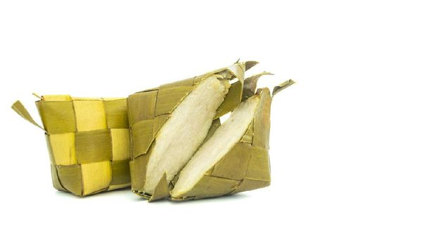 Ketupat or rice dumpling made from rice wrapped in woven young coconut leaves for cooking rice. Special food during Eid Mubarak celebration in Indonesia, isolated on white background with copy space
