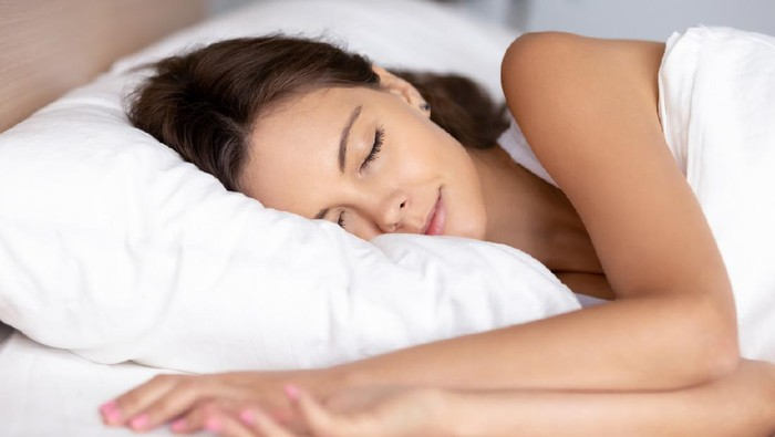 Serene calm young woman sleeping well on orthopedic soft pillow under warm duvet in comfortable cozy fresh bed having good night peaceful healthy sleep enjoying nap dreams resting enough concept