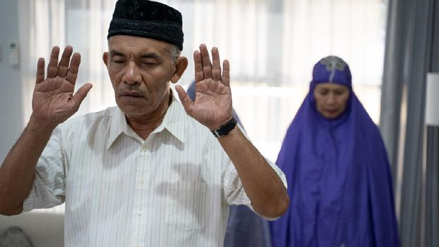 senior old asian muslim male leading a praying in congregation in the house