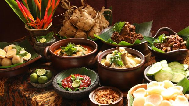 Ketupat Lebaran, the traditional celebratory dish of rice cake with rich side dishes, commonly serving during Eid celebrations. The common side dishes are Beef Rendang (Beef Dry Stew), Beef Liver in Spicy Gravy, Spicy Vegetable Soup, Chicken Curry Soup, and Marbled Soy Egg; while the condiments are fried shallots, shrimp crackers, and red chili sauce. Each dish is plated individually and arranged buffet style on a table; ready to be plated for serving. A vase of decorative banana flowers is used to decorate the table.