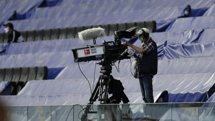 Cameraman wearing a face mask looks not his camera standing by covered seats prior the German Bundesliga soccer match between Eintracht Frankfurt and Borussia Moenchengladbach in Frankfurt, Germany, Saturday, March 16, 2020. The German Bundesliga becomes the worlds first major soccer league to resume after a two-month suspension because of the coronavirus pandemic. (AP Photo/Michael Probst, Pool)