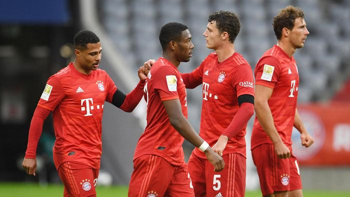 MUNICH, GERMANY - MAY 23: Serge Gnabry, Benjamin Pavard and Alphonso Davies of FC Bayern Muenchen celebrate their sides fifth goal which came through a Martin Hinteregger (not pictured) own goal during the Bundesliga match between FC Bayern Muenchen and Eintracht Frankfurt at Allianz Arena on May 23, 2020 in Munich, Germany. (Photo by Andreas Gebert/Pool via Getty Images)
