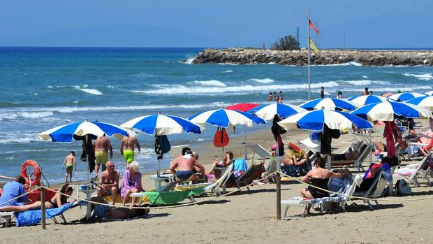 People enjoy a sunny day at an establishment on the beach in Tuscany's Castiglione della Pescaia, Italy, Sunday, May 24, 2020. Europeans and Americans soaked up the sun where they could, taking advantage of the first holiday weekend since coronavirus restrictions were eased, while European governments grappled with how and when to safely let in foreign travelers to salvage the vital summer tourist season. Italy, which plans to open regional and international borders on June 3 in a bid to boost tourism, is only now allowing locals back to beaches in their own regions — with restrictions. (Jennifer Lorenzini/LaPresse via AP)