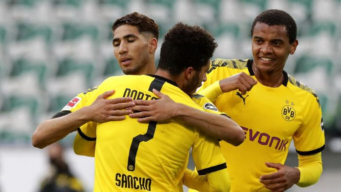 Dortmunds Achraf Hakimi, left, celebrates with Jadon Sancho after scoring his sides second goal during the German Bundesliga soccer match between VfL Wolfsburg and Borussia Dortmund in Wolfsburg, Germany, Saturday, May 23, 2020. The German Bundesliga is the worlds first major soccer league to resume after a two-month suspension because of the coronavirus pandemic. (AP Photo/Michael Sohn, Pool)