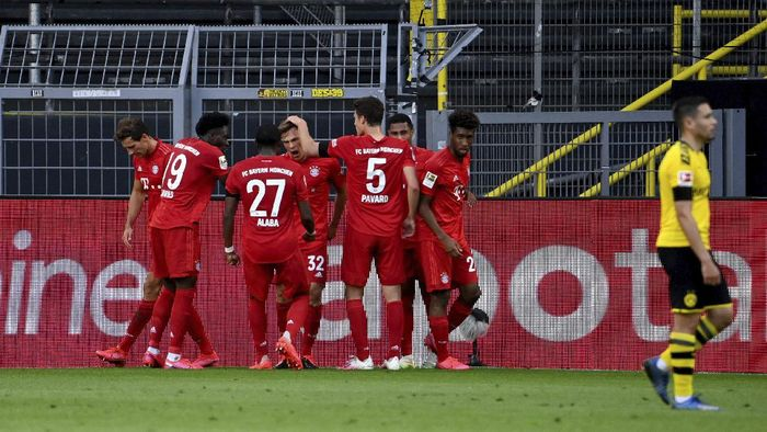 Munichs scorer Joshua Kimmich, center, and his teammates celebrate the opening goal during the German Bundesliga soccer match between Borussia Dortmund and FC Bayern Munich in Dortmund, Germany, Tuesday, May 26, 2020. The German Bundesliga is the worlds first major soccer league to resume after a two-month suspension because of the coronavirus pandemic. (Federico Gambarini/DPA via AP, Pool)