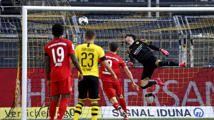 Dortmunds goalkeeper Roman Buerki, right, fails to safe a shot by Munichs Joshua Kimmich during the German Bundesliga soccer match between Borussia Dortmund and FC Bayern Munich in Dortmund, Germany, Tuesday, May 26, 2020. The German Bundesliga is the worlds first major soccer league to resume after a two-month suspension because of the coronavirus pandemic. (Federico Gambarini/DPA via AP, Pool)