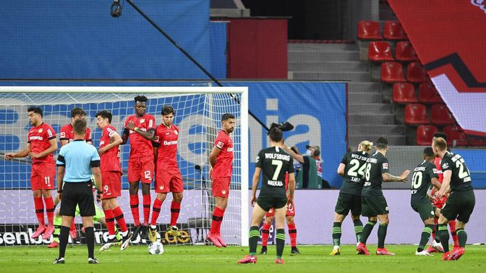Wolfsburgs Maximilian Arnold, right, scores his sides second goal during the German Bundesliga soccer match between Bayer 04 Leverkusen and VfL Wolfsburg in Leverkusen, Germany, Tuesday, May 26, 2020. The German Bundesliga is the worlds first major soccer league to resume after a two-month suspension because of the coronavirus pandemic. (Marius Becker/DPA via AP, Pool)