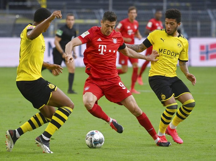 Munichs Robert Lewandowski, center, and Dortmunds Jadon Sancho, right, challenge for the ball during the German Bundesliga soccer match between Borussia Dortmund and FC Bayern Munich in Dortmund, Germany, Tuesday, May 26, 2020. The German Bundesliga is the worlds first major soccer league to resume after a two-month suspension because of the coronavirus pandemic. (Federico Gambarini/DPA via AP, Pool)