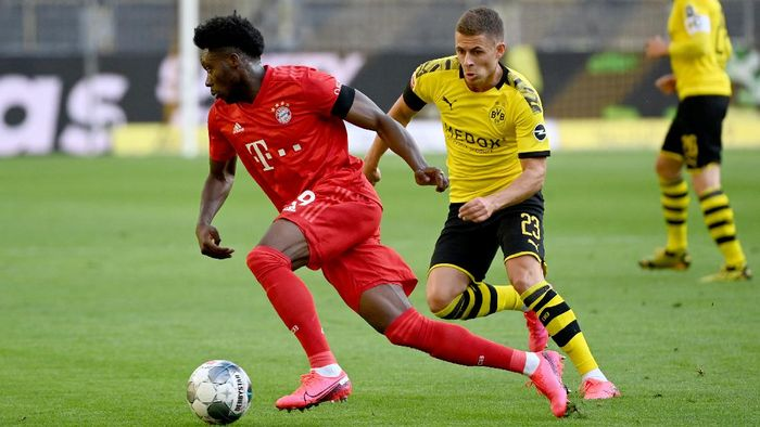 DORTMUND, GERMANY - MAY 26: Alphonso Davies of Bayern Munich is challenged by Thorgan Hazard of Borussia Dortmund during the Bundesliga match between Borussia Dortmund and FC Bayern Muenchen at Signal Iduna Park on May 26, 2020 in Dortmund, Germany. (Photo by Federico Gambarini/Pool via Getty Images)