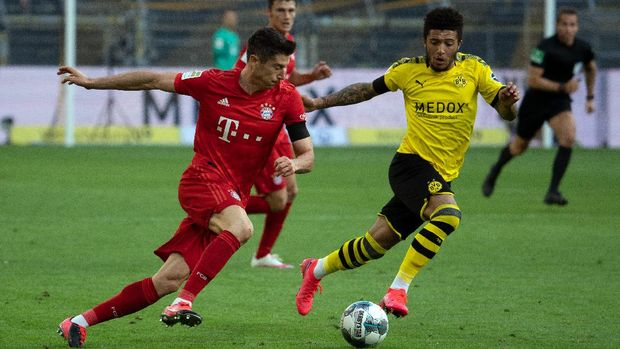 Bayern Munich's Polish forward Robert Lewandowski (L) and Dortmund's English midfielder Jadon Sancho vie for the ball during the German first division Bundesliga football match BVB Borussia Dortmund v FC Bayern Munich on May 26, 2020 in Dortmund, western Germany. (Photo by Federico GAMBARINI / POOL / AFP) / DFL REGULATIONS PROHIBIT ANY USE OF PHOTOGRAPHS AS IMAGE SEQUENCES AND/OR QUASI-VIDEO
