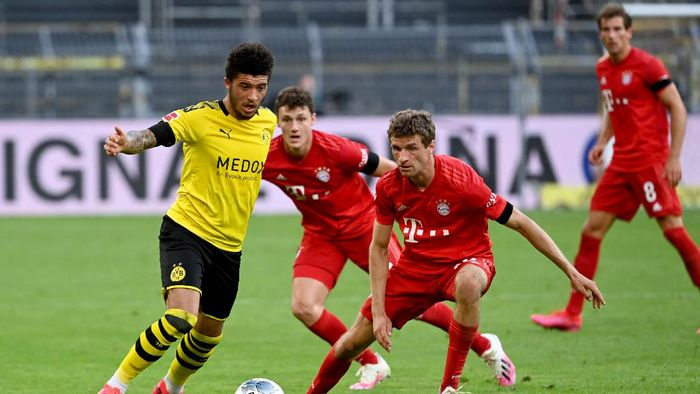 DORTMUND, GERMANY - MAY 26: Jadon Sancho of Borussia Dortmund is challenged by Thomas Muller of Bayern Munich during the Bundesliga match between Borussia Dortmund and FC Bayern Muenchen at Signal Iduna Park on May 26, 2020 in Dortmund, Germany. (Photo by Federico Gambarini/Pool via Getty Images)