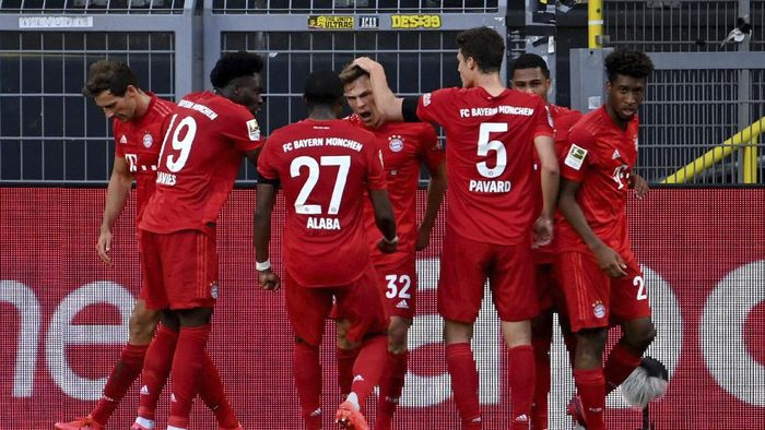 Munichs scorer Joshua Kimmich, center, and his teammats celebrate the opening goal during the German Bundesliga soccer match between Borussia Dortmund and FC Bayern Munich in Dortmund, Germany, Tuesday, May 26, 2020. The German Bundesliga is the worlds first major soccer league to resume after a two-month suspension because of the coronavirus pandemic. (Federico Gambarini/DPA via AP, Pool)