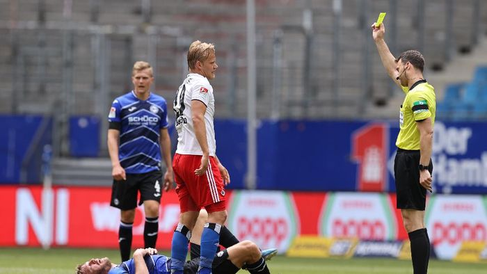 HAMBURG, GERMANY - MAY 24: Referee Felix Zwayer shows Joel Pohjanpalo of Hamburger a yellow card after a foul against Fabian Klos of Bielefeld during the Second Bundesliga match between Hamburger SV and DSC Arminia Bielefeld at Volksparkstadion on May 24, 2020 in Hamburg, Germany. (Photo by Christian Charisius/Pool via Getty Images)