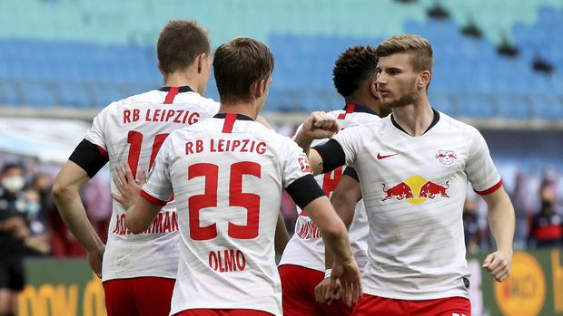 Leipzig's Lukas Klostermann, left, celebrates with team mates and Timo Werner, right, after his side's opening goal during the German Bundesliga soccer match between RB Leipzig and Hertha BSC at the Red Bull Arena in Leipzig, Germany, Wednesday, May 27, 2020. The German Bundesliga is the world's first major soccer league to resume after a two-month suspension because of the coronavirus pandemic. (Alexander Hassenstein/Pool via AP)