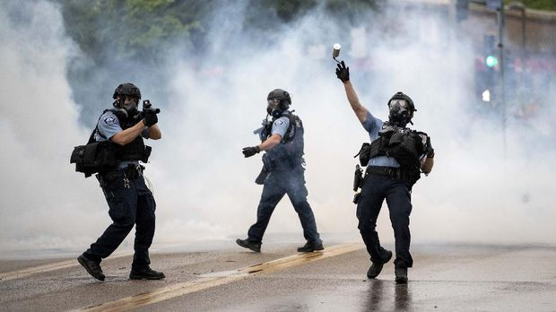 A police officer throws a tear gas canister towards protesters at the Minneapolis 3rd Police Precinct, following a rally for George Floyd on Tuesday, May 26, 2020, in Minneapolis. Four Minneapolis officers involved in the arrest of Floyd, a black man who died in police custody, were fired Tuesday, hours after a bystander's video showed an officer kneeling on the handcuffed man's neck, even after he pleaded that he could not breathe and stopped moving. (Richard Tsong-Taatarii/Star Tribune via AP)