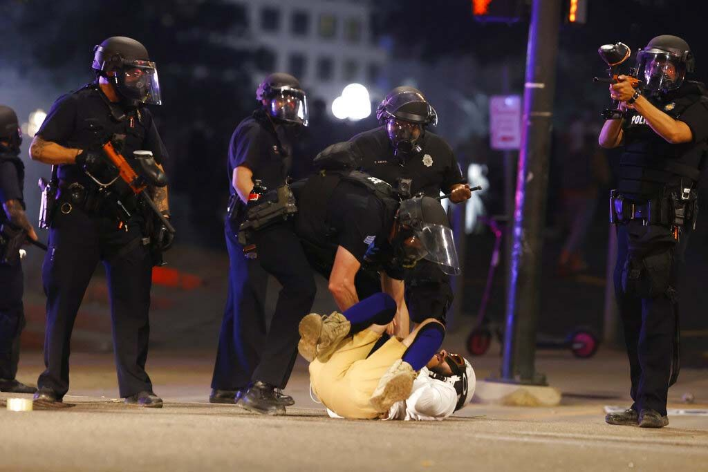 Denver Police Department officers stand over a man who fell to the street after they used tear gas and rubber bullets to disperse a protest outside the State Capitol over the death of George Floyd, a handcuffed black man who died in police custody in Minneapolis, late Thursday, May 28, 2020, in Denver. (AP Photo/David Zalubowski)