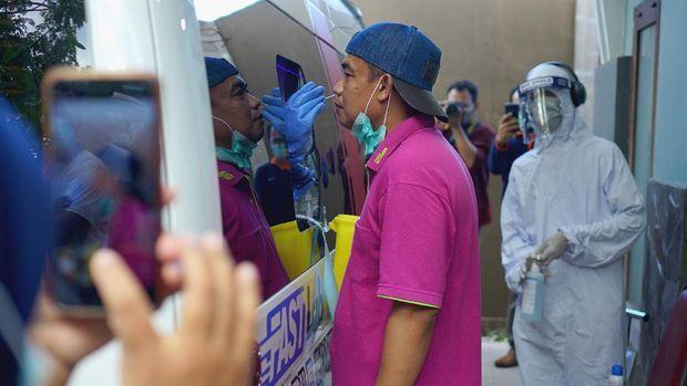 Petugas mengambil sampel lendir dengan teknik swab hidung dan tenggorokan kepada peserta tes PCR (Polymerase Chain Reaction) keliling di Tulungagung, Jawa Timur, Jumat (29/5/2020). Lebih dari 200 orang yang terdiri dari tenaga medis di RSUD dr Iskak Tulungagung dan tiga puskesmas penyangga COVID-19, serta pasien berstatus PDP yang dkarantina di Rusunawa IAIN Tulungagung, diperiksa sampel lendir tenggorokannya untuk mendeteksi infeksi virus Corona atau SARS-Cov-2. ANTARA FOTO/Destyan Sujarwoko/wsj.