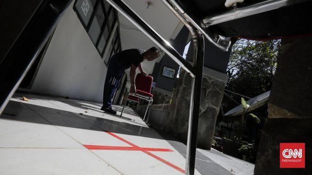 Staf SMKN 26 Rawamangun, Jakarta Timur, menyiapkan bangku antrean dengan jarak sosial dalam persiapan pelayanan Posko Penerimaan Peserta Didik Baru 2020 dengan standar pencegahan penyebaran pandemi Covid-19,  Sabtu, 30 Mei 2020. Persiapan ini dilakukan SMKN 26 Rawamangun  yang ditunjuk sebagai posko PPDB untuk melayani peserta penerimaan calon peserta didik sejumlah sekolah di area Timur I. CNN Indonesia/Adhi Wicaksono
