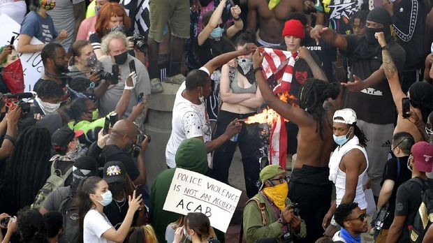 Demonstrators light an American flag on fire during a protest, Friday, May 29, 2020 in Atlanta. The protest started peacefully earlier in the day before demonstrators clashed with police. (AP Photo/Mike Stewart)