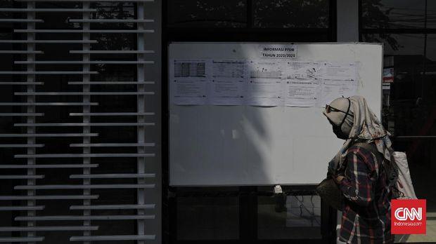 Orang tua murid melihat pengumuman di SMKN 26 Rawamangun, Jakarta Timur, menggunakan ruang disinfektan kreasi sekolah itu yang menggunakan sensor gerak dan tenaga surya dalam rangka pelayanan penerimaan peserta didik baru (PPDB) 2020 dengan standar pencegahan penyebaran pandemi Covid-19,  Sabtu, 30 Mei 2020. Persiapan ini dilakukan SMKN 26 Rawamangun  yang ditunjuk sebagai posko PPDB untuk melayani peserta penerimaan calon peserta didik sejumlah sekolah di area Timur I. CNN Indonesia/Adhi Wicaksono