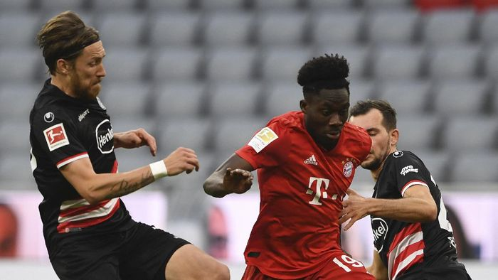 Bayerns Alphonso Davies, center, and  Duesseldorfs Kevin Stoeger challenge for the ball during the German Bundesliga soccer match between FC Bayern Munich and Fortuna Duesseldorf in Munich, Germany, Saturday, May 30, 2020. Because of the coronavirus outbreak all soccer matches of the German Bundesliga take place without spectators. (Christof Stache/Pool via AP)