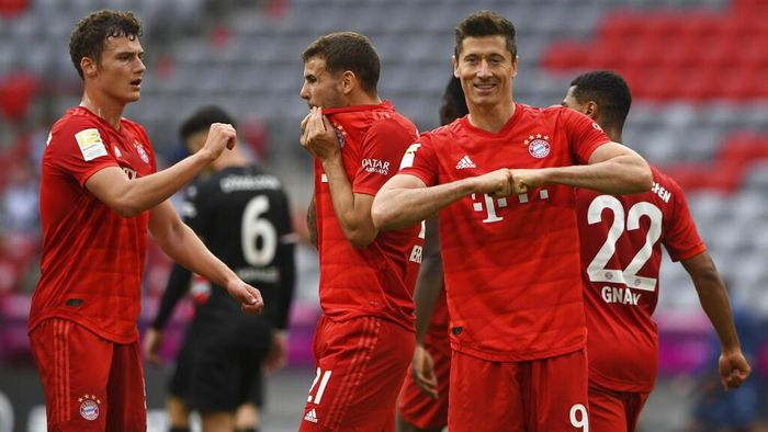 Munich players, from left, Benjamin Pavard, Lucas Hernandez and Robert Lewandowski, celebrate taking the score to  3:0 against Fortuna Dsseldorf, during their Bundesliga soccer match played without an audience in Munich, Germany, Saturday May 30, 2020. Soccer matches are being played without an audience because of the coronavirus pandemic. (Christof Stache/Pool via AP)
