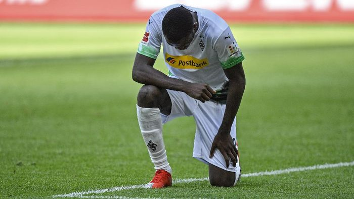 Moenchengladbachs Marcus Thuram taking the knee after scoring his sides second goal during the German Bundesliga soccer match between Borussia Moenchengladbach and Union Berlin in Moenchengladbach, Germany, Sunday, May 31, 2020. The German Bundesliga becomes the worlds first major soccer league to resume after a two-month suspension because of the coronavirus pandemic. (AP Photo/Martin Meissner, Pool)