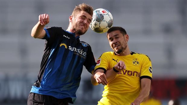Paderborn's German forward Dennis Srbeny vies with Dortmund's Portuguese defender Raphael Guerreiro during the German first division Bundesliga football match SC Paderborn 07 and Borussia Dortmund at Benteler Arena in Paderborn on May 31, 2020. - Paderborn's German forward Dennis Srbeny vies with Dortmund's Portuguese defender Raphael Guerreiro (Photo by Lars Baron / POOL / AFP) / DFL REGULATIONS PROHIBIT ANY USE OF PHOTOGRAPHS AS IMAGE SEQUENCES AND/OR QUASI-VIDEO