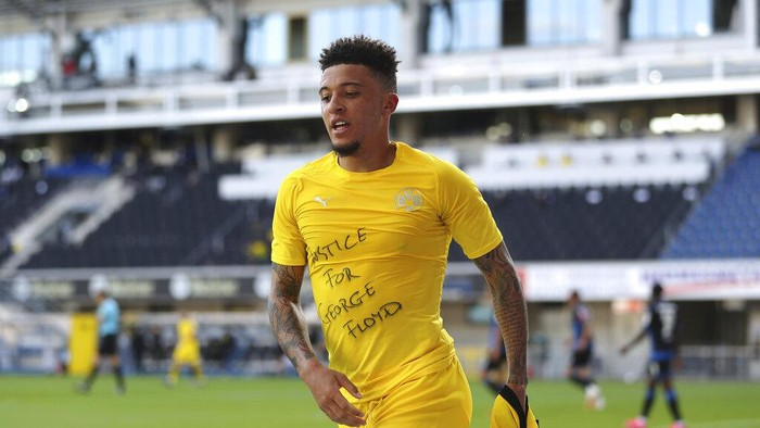 Jadon Sancho of Borussia Dortmund celebrates scoring his teams second goal of the game with a Justice for George Floyd shirt during the German Bundesliga soccer match between SC Paderborn 07 and Borussia Dortmund at Benteler Arena in Paderborn, Germany, Sunday, May 31, 2020. Because of the coronavirus outbreak all soccer matches of the German Bundesliga take place without spectators. (Lars Baron/Pool via AP)