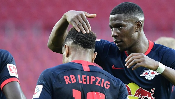 Leipzigs French midfielder Christopher Nkunku, left, celebrates with Leipzigs French defender Nordi Mukiele after he scores his side second goal during the German Bundesliga soccer match between 1. FC Cologne and RB Leipzig, in Cologne, Germany, Monday, June 1, 2020. Because of the coronavirus outbreak all soccer matches of the German Bundesliga take place without spectators. (Ina Fassbender/Pool via AP)