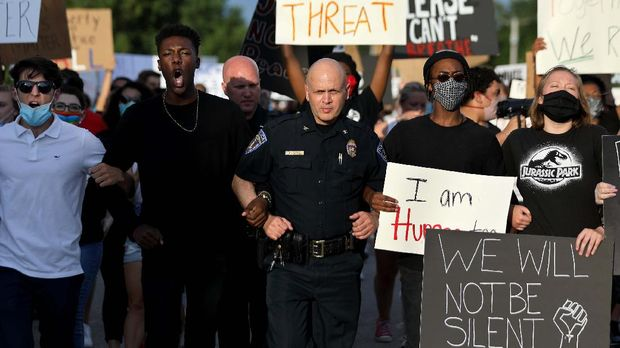 O'Fallon (Mo.) police Chief Tim Clothier, center, walks arm-in-arm with Ryan Staples, left, and Jalen Thompson, right, at the front of a march for George Floyd in O
