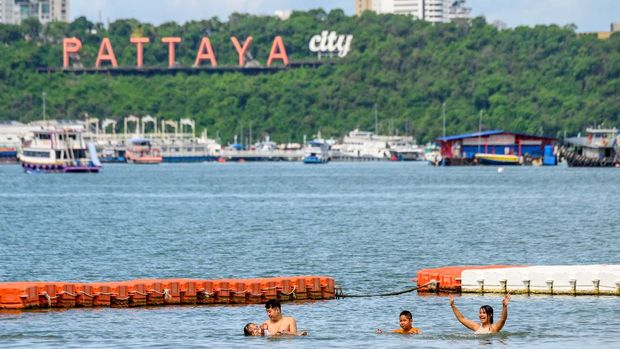 People take a dip in the water at the main beach in Pattaya on June 1, 2020. - People flocked back to some of Thailand's famed sandy beaches June 1, keeping well apart but enjoying the outdoors, as authorities lifted coronavirus restrictions for the first time in more than two months. (Photo by Mladen ANTONOV / AFP)