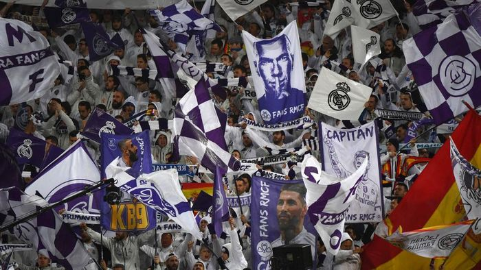 Real Madrid fans holding pictures of Real Madrids French coach Zinedine Zidane (top), Real Madrids Spanish defender Sergio Ramos (R) and Real Madrids French forward Karim Benzema (L) cheer for their team before the Spanish League football match between Real Madrid and Barcelona at the Santiago Bernabeu stadium in Madrid on March 1, 2020. (Photo by GABRIEL BOUYS / AFP)