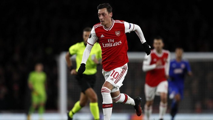 Arsenals German midfielder Mesut Ozil runs with the ball during the UEFA Europa league round of 32 second leg football match between Arsenal and Olympiakos at the Emirates stadium in London on February 27, 2020. (Photo by Adrian DENNIS / AFP)