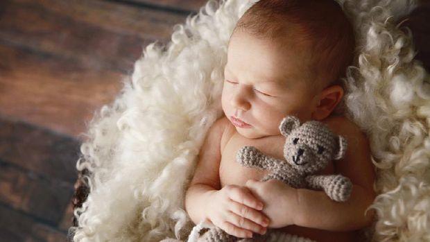 A beautiful newborn baby boy hugs a little teddy bear as he sleeps. He is lying on a soft blanket of curly wool.