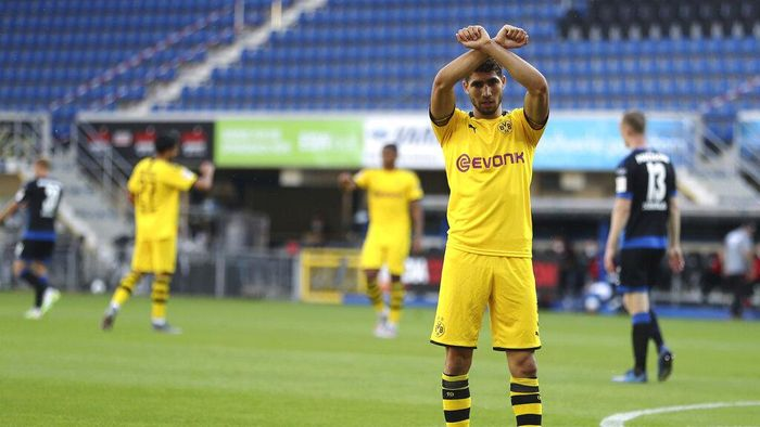 Achraf Hakimi Mouh of Borussia Dortmund celebrates scoring his teams fourth goal of the game during the German Bundesliga soccer match between SC Paderborn 07 and Borussia Dortmund at Benteler Arena in Paderborn, Germany, Sunday, May 31, 2020. Because of the coronavirus outbreak all soccer matches of the German Bundesliga take place without spectators. (Lars Baron/Pool via AP)