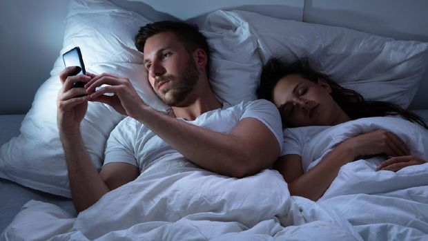 Young Man Using Cellphone While Her Wife Sitting On Bed At Night