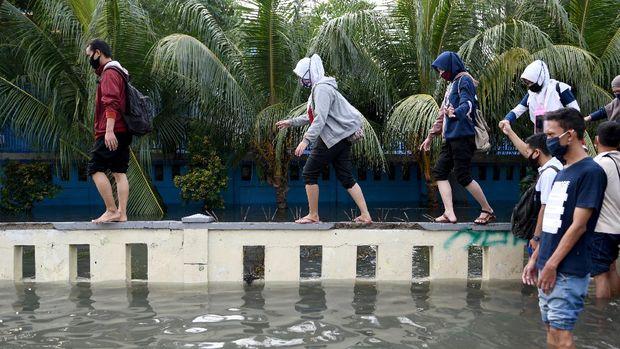 Warga meniti pagar menghindari banjir air rob di kawasan Muara Baru, Penjaringan, Jakarta Utara, Jumat (5/6/2020). Menurut Badan Meteorologi, Klimatologi, dan Geofisika (BMKG) rob disebabkan oleh kondisi pasang air laut yang cukup tinggi di beberapa wilayah Indonesia akibat fase bulan purnama. ANTARA FOTO/M Risyal Hidayat/wsj.