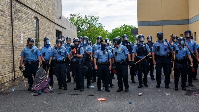 (FILES) In this file photo taken on May 27, 2020 Minneapolise Police officers stand in a line while facing protesters demonstrating against the death of George Floyd outside the 3rd Precinct Police Precinct in Minneapolis, Minnesota. - Members of the Minneapolis City Council announced on June 7, 2020 that they intend to disband the citys police department, US media reported. (Photo by Kerem Yucel / AFP)